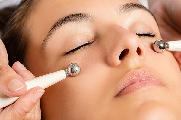 Photo of a woman receiving a microcurrent facial treatment