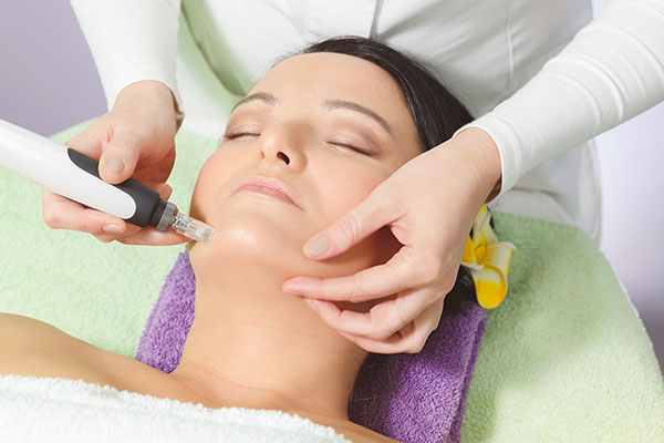 Photo of a woman receiving a micro-needling treatment on her chin